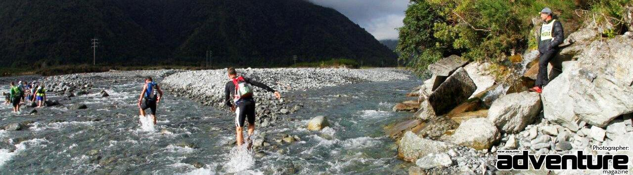 Runners crossing the Mingha River, Steve Gurney watching from nearby rocks